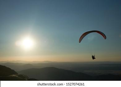 Paragliders flying at sunset over the port of Peña Negra (Peñanegra) located in the Sierra de Villafranca. Avila. Castilla and León. Spain