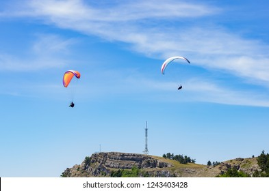 Paragliders soaring above the mountain top. Russia, Republic of Crimea. 06.13.2018. Flight of paragliders over Ai-Petri mountain