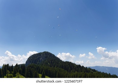 Paragliders soaring high against the blue sky and mountains above Lake Annecy  France