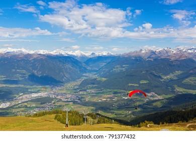 Paragliders take off near ski lift with Austrian Alps mountain range, valley, snowy glacier mountains in background, Autumn view from Mount Kronplatz, South Tyrol, Italy, Europe