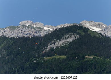 Paragliders taking off and flying around Col de la Forclaz above Lake Annecy  France