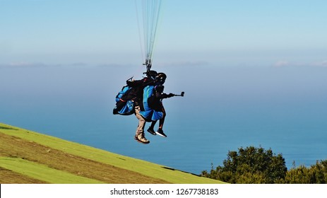 paragliders, tandem shortly after the start, flying 1meter above the ground. An adult and a child, faces not recognizable, the child in front holding a mobile with a staff to record the flight.