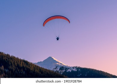 Paragliding above the alps while sunset