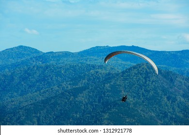 Paragliding in Altai mountains. Paragliders in fight in the mountains, concept of extreme sport activity.