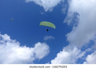 Paragliding in cloudy blue sky. Paraglider colourful tandem flying over deep turquoise mediterranean sea and mountains in bright sunny day