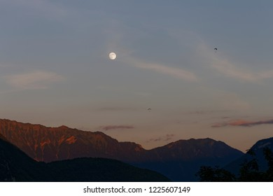 Paragliding in the evening amongst the mountains with the moon in the sky Annecy France