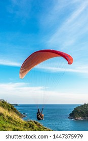 Paragliding Extreme sport, Paraglider flying on the blue sky and white cloud in Summer day at Phuket Sea, Thailand.