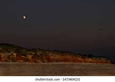 paragliding flying over the beach with full moon