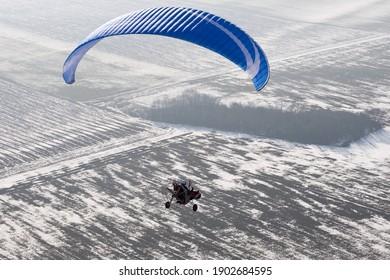 Parapente de buggy motorisée ou paramotrice vue du ciel en France survolant des champs enneigés en hiver