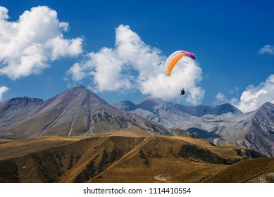 Paragliding in mountains. Extreme sport. Flight on paraglider over mountains of Caucasus.