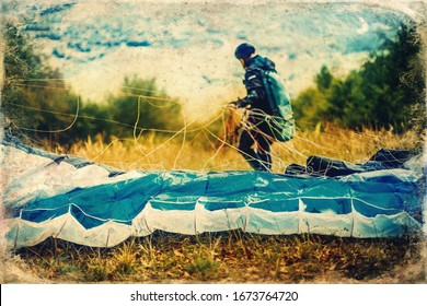Paragliding in the mountains, paraglider on the ground, old photo effect.