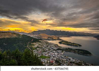 Paragliding over Queenstown and Lake Wakaitipu with The Remarkables in the background from viewpoint at Queenstown Skyline, New Zealand