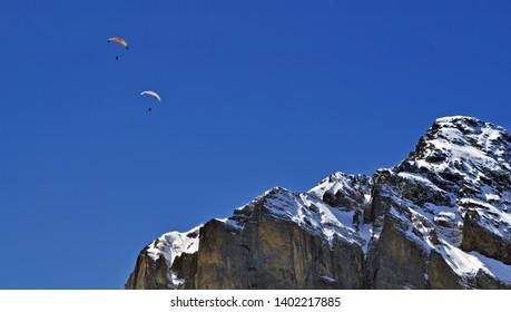 Paragliding over swiss alps peak