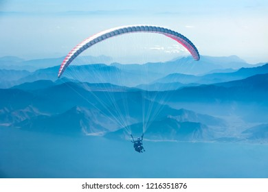 Paragliding. Paraglider flying in the sky over the mountains