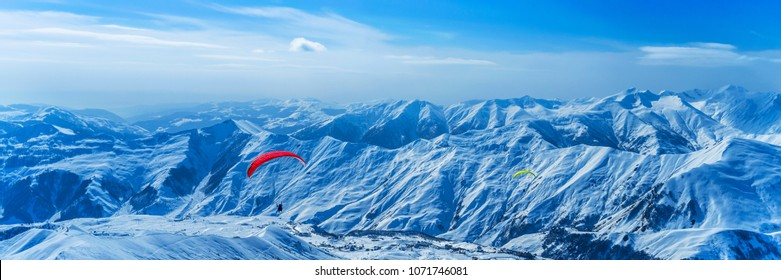 Paragliding. Paragliders fying against snow covered mountains panorama.
