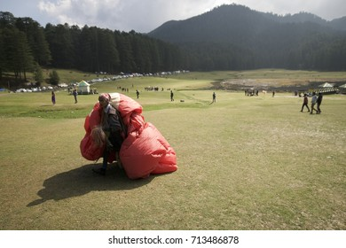 A paragliding pilot is seen carrying his paraglider all the way back to the starting point. Shot on February 2017, at the remote hill station of Khajjiar, in Chamba district, Himachal Pradesh, India.