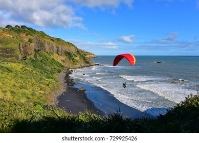Paragliding at scenic Muriwai Beach in North Island, New Zealand