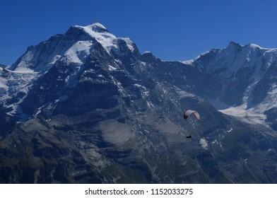 Paragliding from Schilthornwith view to Eiger, Mönch and Jungfrau  in the swiss alps   Ein Gleitschirmflug vom Schilthorn mit Blick auf das Eiger, Mönch und Jungfrau-Panorama