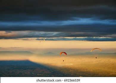 Paragliding silhouette flying over mountain valley in beautiful warm sunset colors,Paragliding over mountains
