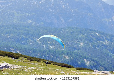 Paragliding in the sky. Paraglider flying over the sky with blue water and mountains in bright sunny day. Aerial view of paraglider and Blue Lagoon in Hallstatt, Austria. Extreme sport. Landscape