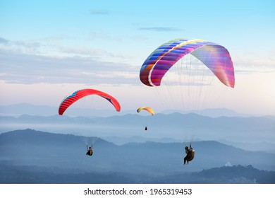 Paragliding in the sky. Paraglider  flying over Landscape sun set Concept of extreme sport, taking adventure challenge.