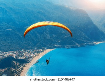 Paragliding in the sky. Paraglider tandem flying over the sea with blue water, beach and mountains in sunrise. Aerial view of paraglider and Blue Lagoon in Oludeniz, Turkey. Extreme sport. Landscape