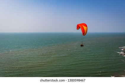 Paragliding in the sky. Paraglider tandem flying over the sea with blue water and mountains in bright sunny day. Aerial view of paraglider and Blue Lagoon in goa India at . Extreme sport. Landscape