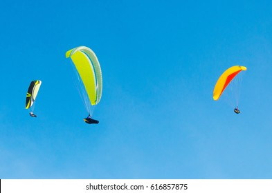 Paragliding in the sky. three paraglider fly over the mountain valley. Competitions with paragliding, Russia, Siberia