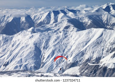 Paragliding at snowy mountains over ski resort at sunny winter day. Caucasus Mountains. Georgia, region Gudauri.