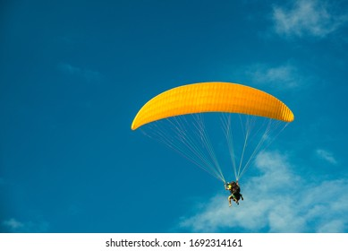 paragliding, yellow parapente on the blue sky