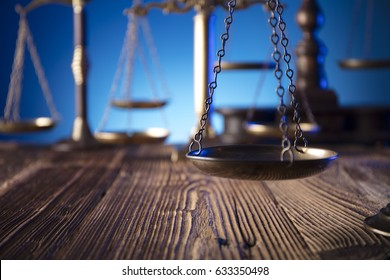 Paragraph symbol, book and judge's gavel on wooden table. Variety of scales of justice in bokeh on blue background. Law concept background