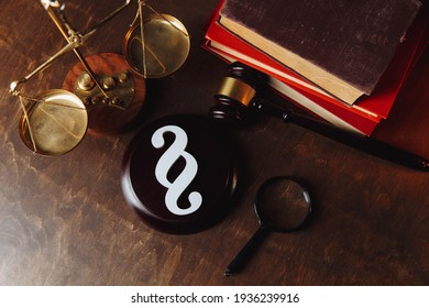 Paragraph symbol and judge gavel with scales and books at lawyer office. Top view