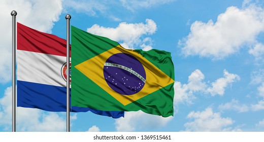 Paraguay and Brazil flag waving in the wind against white cloudy blue sky together. Diplomacy concept, international relations.