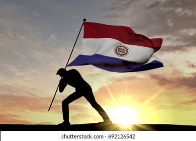 Paraguay flag being pushed into the ground by a male silhouette. 3D Rendering