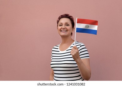 Paraguay flag. Woman holding Paraguayan flag. Nice portrait of middle aged lady 40 50 years old with a national flag over pink wall background outdoors.