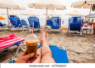 Paralia, Greece - June 11, 2013: Man sitting on the blue deckchair with ice coffee in hand on the Paralia beach on Aegean Sea coast in Greece