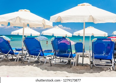 Paralia, Greece - June 15, 2013: Blue deckchairs, white sun umbrellas parasols, resting tourists on the beaches of Greek Paralia resort city with warm Aegean sea on the background