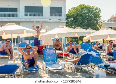 Paralia, Greece - June 15, 2013: Man sitting and standing in various poses on the blue deckchairs under white parasols sun umbrellas on the beach using multiple exposure photography technique