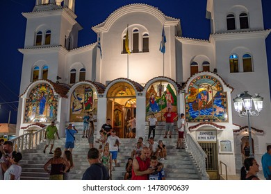 Paralia Katerini, Greece, July 2019: St. Fotini Church or St. Paraskevi Church located on the beach in Paralia resort, Greece. People tourist walking by the street in central Macedonia, Pieria, Greece