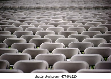 Parallel arranged empty seat rows of folding chairs on a lawn before a concert / Rows of Seats at Concert