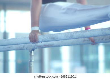Parallel bars gymnastic competition. Focus on first bar and blurry background to increase the effect of movement. Abstract image, symbol of strength, health, power, endurance.
