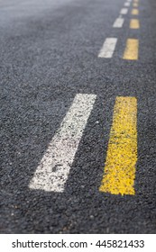 Parallel dashed road lines in white and yellow