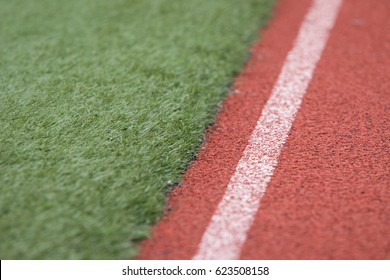 Parallel lines of red brick crumbled rubber running track with faded white lane marker along worn and matted green fake astroturf field at amateur youth sporting event