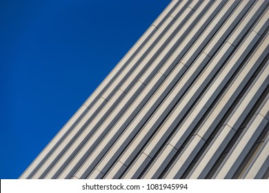 Parallel lines for the side of a highrise building under a deep blue sky.