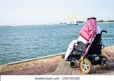 a paralyzed Arab man is siting on a wheelchair front of sea and looking towards the ocean