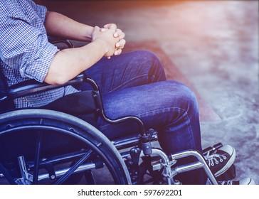 Paralyzed man praying on  his wheelchair, sepia tone