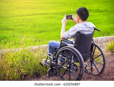 Paralyzed man using smart phone on his wheelchair against green field background