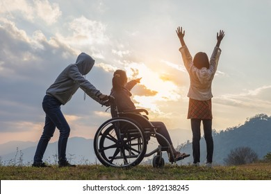 Paralyzed woman sitting on her wheelchair with her daughter and care helper at sunset