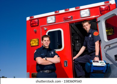 Paramedic by door of ambulance by colleague, portrait, low angle view