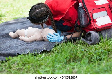 Paramedic demonstrate Cardiopulmonary resuscitation (CPR) on baby dummy. First aid training.